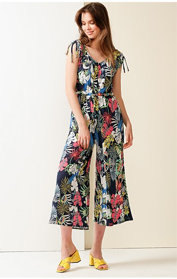 COLUMBUS CIRCLE STRETCH JERSEY WIDE LEG ADJUSTABLE JUMPSUIT IN NAVY TROPICAL PRINT